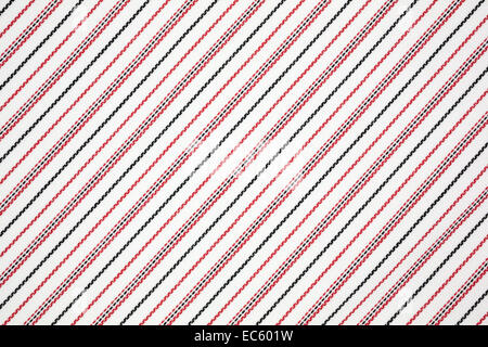 A very close view of red and black fabric woven into a light background. - Stock Photo