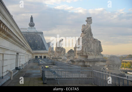 Paris sky from the roof of the Musee d'Orsay , statues in the soft evening light - Stock Photo