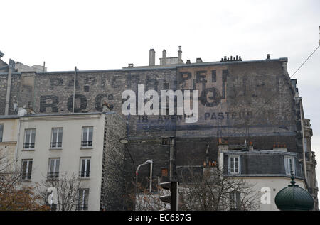 Old painted avert for Rochefort on a brick building in Paris - Stock Photo