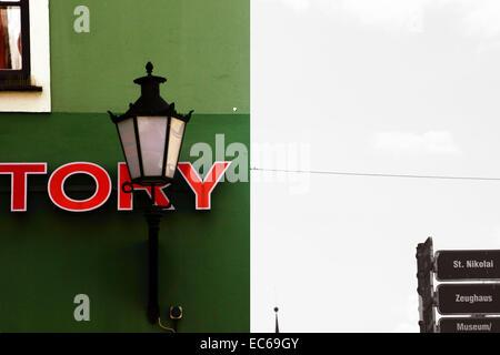 Nostalgic lamp in front of a green house facade - Stock Photo