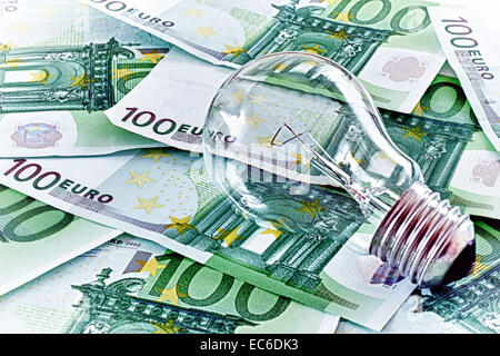 Expensive energy non saving light bulb and paper money - Stock Photo