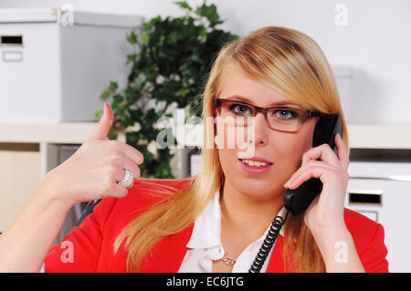 young woman calling with uplifted thumb in the office - Stock Photo