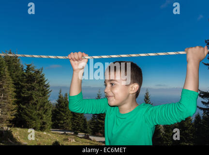 8 year old child climbing trees in The Austrian Alps - Stock Photo