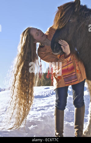 woman with long light brown hair hugging iceland horse - Stock Photo