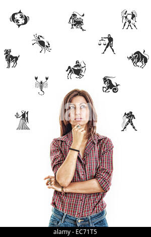 Ordinary casual beautiful woman surrounded with zodiac signs thoughtfully looking up with questionable face expression - Stock Photo