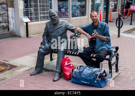 Man sitting on bench beside statue of former mayor, Reverend Gaetz, Red Deer. Alberta, Canada - Stock Photo