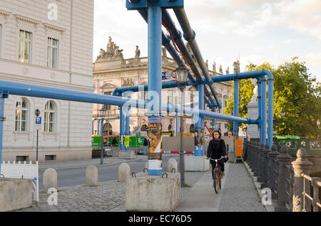BERLIN, GERMANY - SEPTEMBER 29: A young bicyclist on a sidewalk with painted blue pipes for drainage construction - Stock Photo