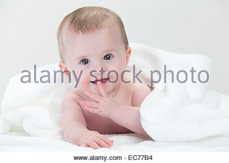 Smiling baby laying on towel - Stock Photo