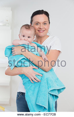 Smiling mother holding baby wrapped in a towel - Stock Photo