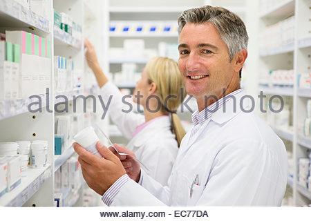 Pharmacists holding bottle of prescription medication in pharmacy - Stock Photo