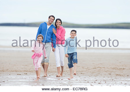 Family walking together on beach - Stock Photo