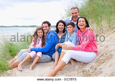 Multi-generation family smiling on sand dune - Stock Photo