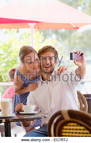 Couple taking selfie in outdoor cafe - Stock Photo