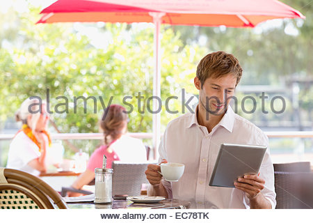 Man drinking coffee with digital tablet in outdoor cafe - Stock Photo