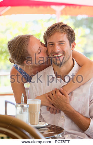 Portrait of woman kissing man at outdoor cafe - Stock Photo
