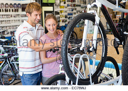 Couple choosing a bicycle in shop - Stock Photo