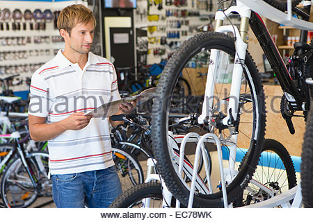 Man choosing a bicycle in shop - Stock Photo