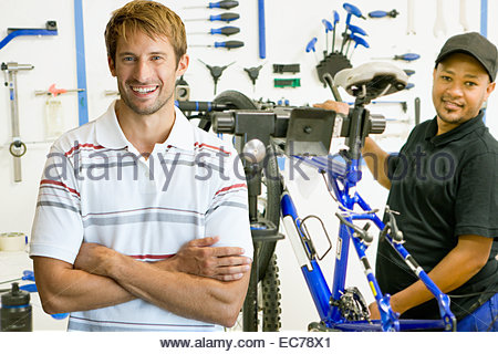 Portrait of store manager and cycle technician in workshop - Stock Photo