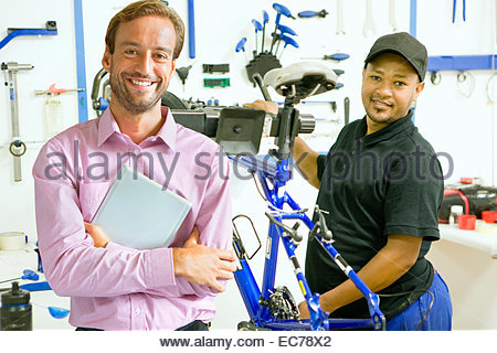 Portrait of store owner and cycle technician in workshop - Stock Photo