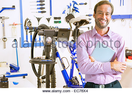 Shop owner in bicycle workshop - Stock Photo
