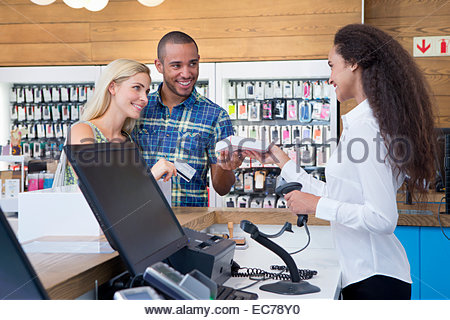 Couple making a purchase from store assistant in shop - Stock Photo