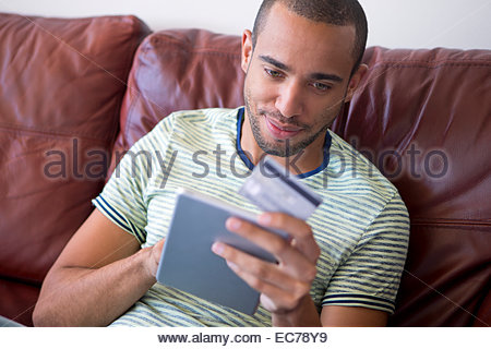 Man relaxing on sofa and making a purchase on digital tablet - Stock Photo