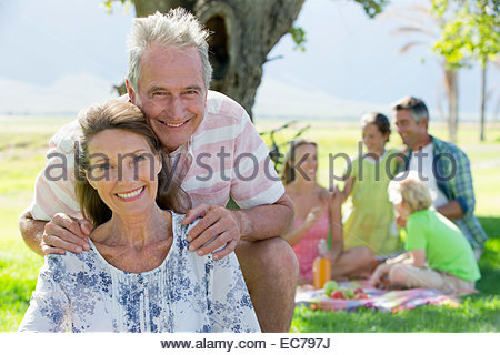 Senior couple and Multi generation family having a picnic in countryside - Stock Photo