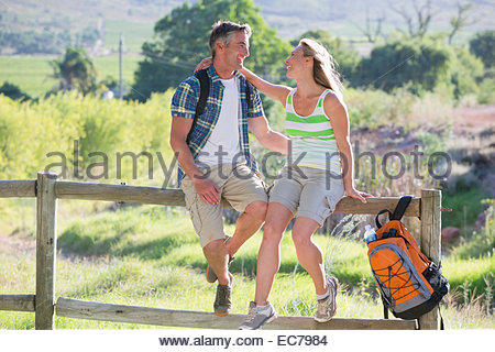 Couple resting on a fence in a rural setting - Stock Photo