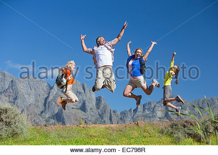 Family jumping in the air on a mountain hiking trail - Stock Photo