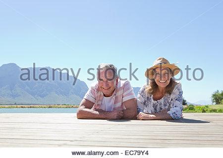 Senior couple lying on wooden jetty - Stock Photo