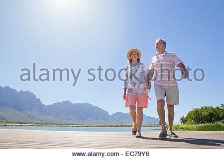 Senior couple walking on wooden jetty - Stock Photo