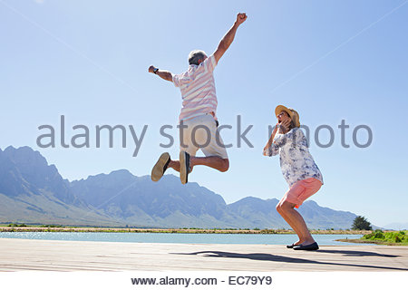 Senior couple on wooden jetty by lake, man jumping - Stock Photo