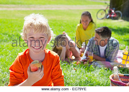 Close-up of boy with apple with family having a picnic in countryside, - Stock Photo