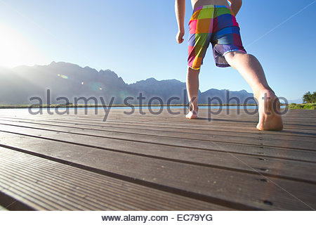 Boy running to jump into a lake from a jetty - Stock Photo