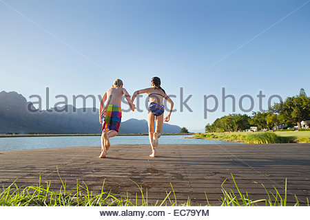 Children in swimwear, running to jump into a lake from a jetty - Stock Photo