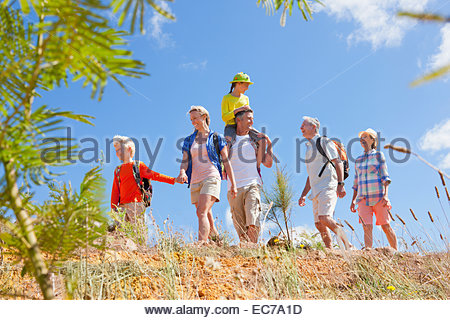 Multi generation family hiking in countryside - Stock Photo