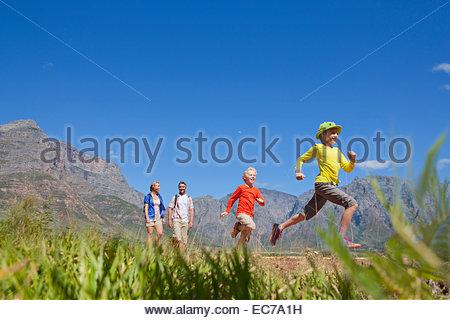 Family hiking on mountain path - Stock Photo