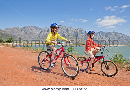 Children riding bicycles on track by lake - Stock Photo