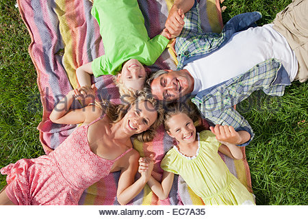 Overhead portrait of a multi generation family lying on the grass - Stock Photo