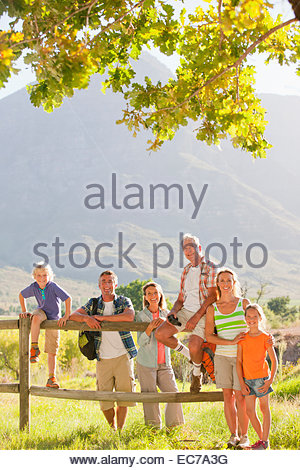 Multi generation family out for walk resting on fence, smiling at camera, in countryside - Stock Photo