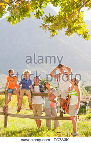 Multi generation family out for walk resting on a fence in a rural setting - Stock Photo