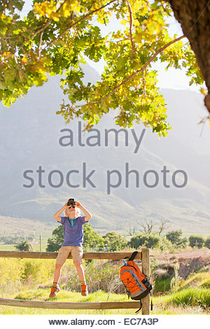 Boy sitting on fence looking through binoculars - Stock Photo