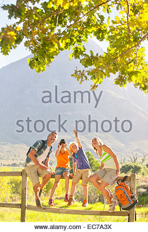Two generation family out for walk resting on fence in countryside - Stock Photo