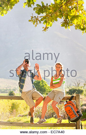 Couple out for walk resting on a fence in countryside - Stock Photo