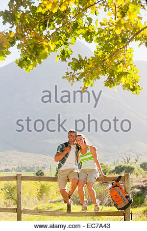 Couple out for walk, smiling at camera, resting on a fence in countryside - Stock Photo
