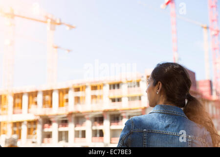 Germany, Berlin, young woman standing in front of construction site - Stock Photo