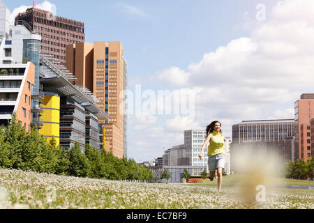 Germany, Berlin, happy young woman running on a meadow near Potsdam Square - Stock Photo