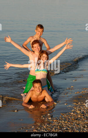 Italy, four children in a row at seafront - Stock Photo