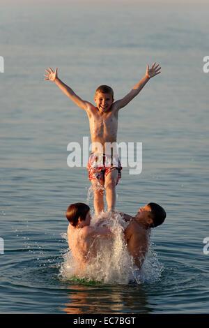 Italy, three teenage boys having fun at seaside - Stock Photo