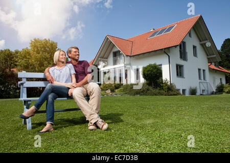 Relaxed mature couple sitting on bench in garden - Stock Photo